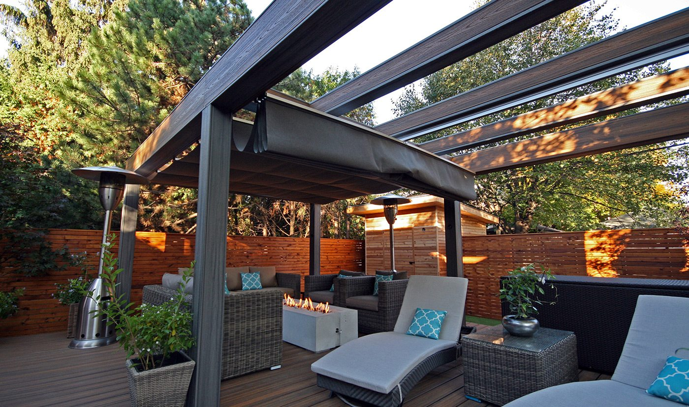 image of a backyard oasis. Complete with a Trex deck, Trex Pergola, cedar fencing, cabana and a retractable shade canopy