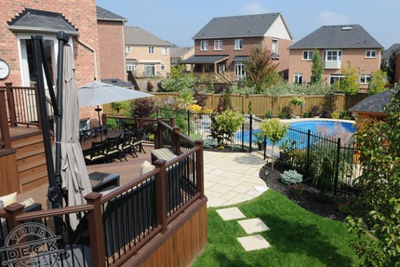 fully finished backyard landscape complete with a deck, stone patio and a pool